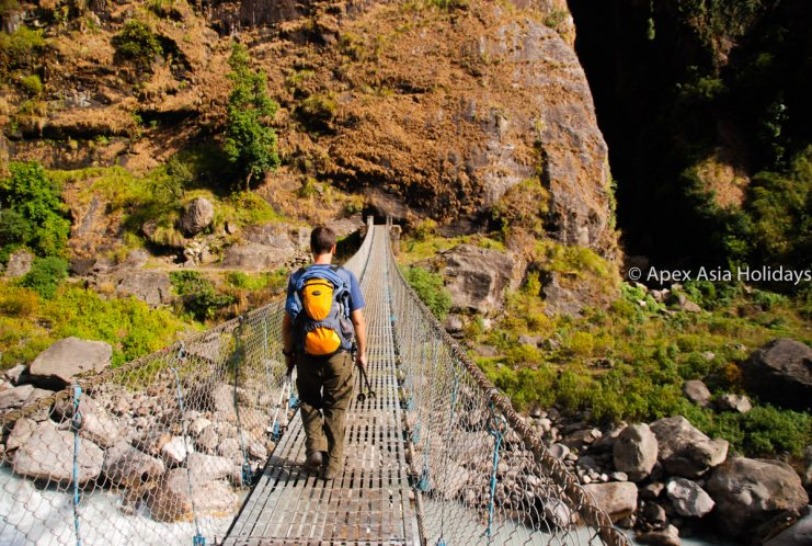 A trekker crossing the suspension bridge along the Annapurna trekking Region