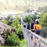 Trekkers and trekking crews crossing a suspension bridge along the Everest Trekking Route
