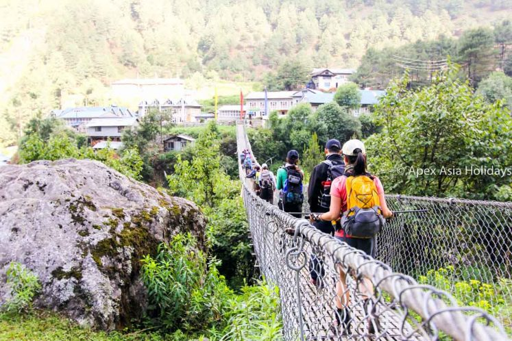Trekkers and trekking crews crossing a suspension bridge along the Everest Trekking Route